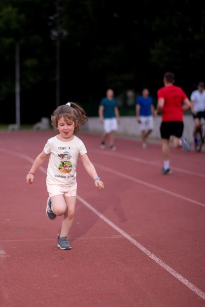 Atletika za decu, devojčica trči na atletskoj stazi u sportanac majici.