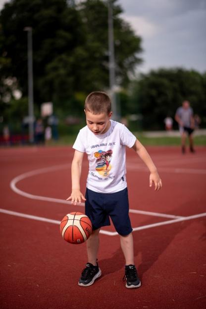 Mali košarkaš vežba košarku na terenu u sportanac majici. Zanimljive sportske dečije ilustracije koje će deci približiti sport.