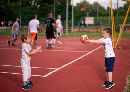 Dečaci se dobacuju sa loptom na košarkaškom terenu i nose sportanac majice.
