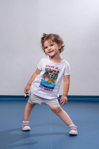 Mala devojčica se smeje u sportanac majici sport je plivati do cilja. Izaberite i vi originazan poklon za vaše mališane.