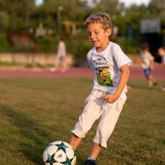 Dečak fudbaler šutira loptu u dečijoj majici sportanac, dečije majice sportanac sa fudbalskim motivima. Izaberi sport budi u stilu.