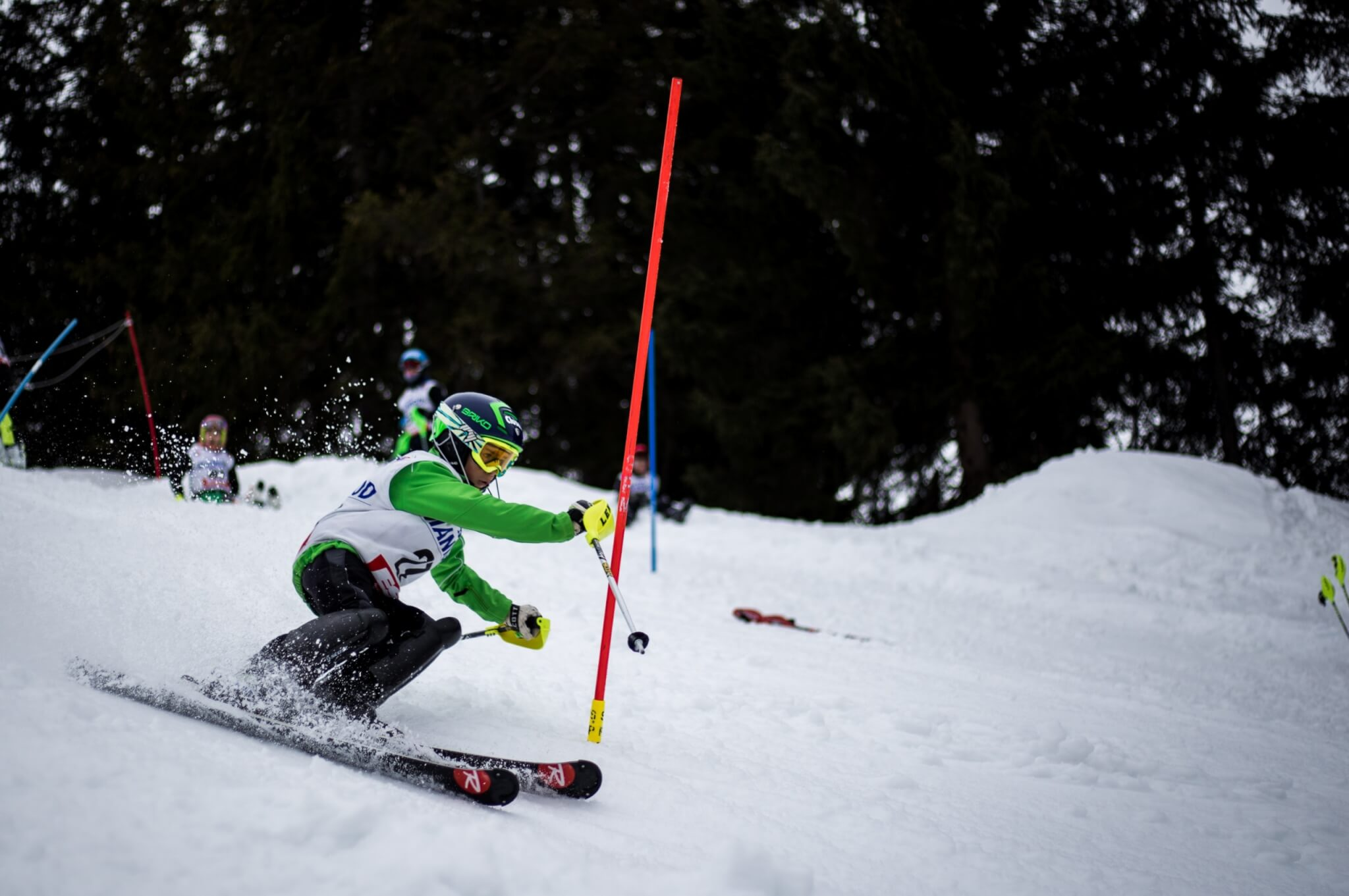 Dečak skija na planini i zaobilazi zastavicu
