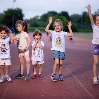 Devojčice se igraju na atletskoj stazi, sportanac majice